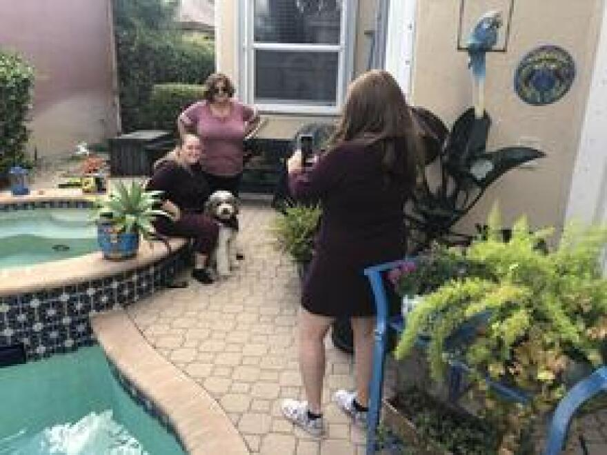 Elyse Claprood takes a photo of her daughter Annabel with Diana Haneski, the librarian at Marjory Stoneman Douglas High School, and River, the therapy dog Haneski brings to the school every day. Annabel has bonded with River, and she invited Haneski to bring the dog to the Claproods' home in Coral Springs for an interview with WLRN.