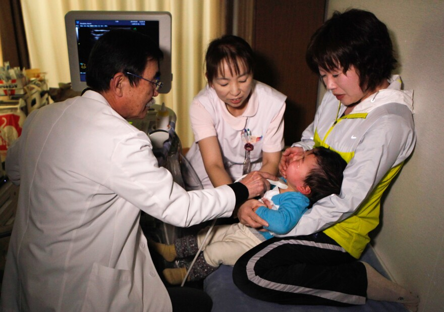 A doctor examines the thyroid of a child at a temporary housing complex in Nihonmatsu, about 31 miles from the tsunami-crippled Fukushima Dai-ichi nuclear power plant, in 2013.