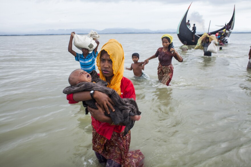 "the U.N. says the Rohingya are ""the most persecuted minority in the world."" Above, refugees cross a river to a temporary camp after crossing from Myanmar to Bangladesh."