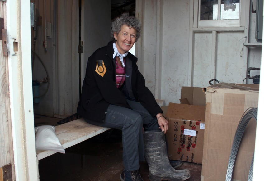 Joan Schrader, the veterinarian on the farm, sits on a bench that creates a staging area for workers to disinfect their boots.