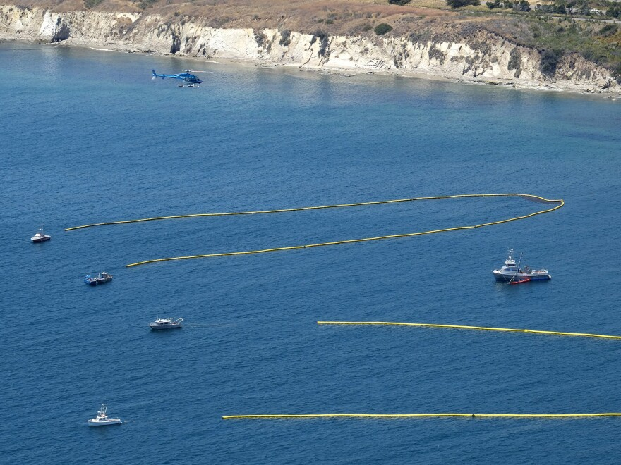 A helicopter coordinates ships below pulling booms to collect oil from a spill near Refugio State Beach, north of Goleta, Calif., on Wednesday.
