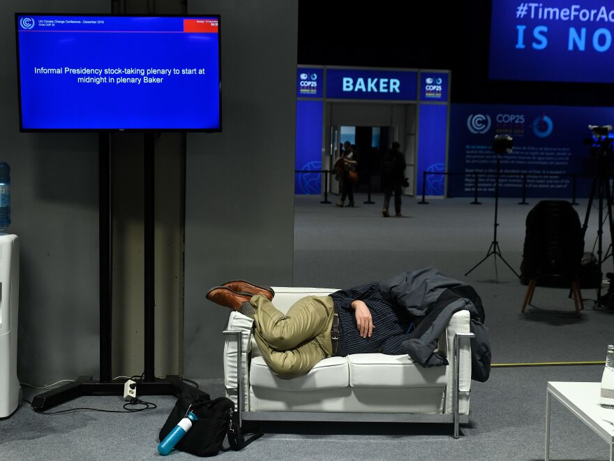 A man takes a nap during the talks in Madrid on Sunday, the longest in 25 years of the U.N. climate change meetings. The chairwoman had scheduled delegates to meet at 1:30 a.m. on Sunday to resume negotiations.