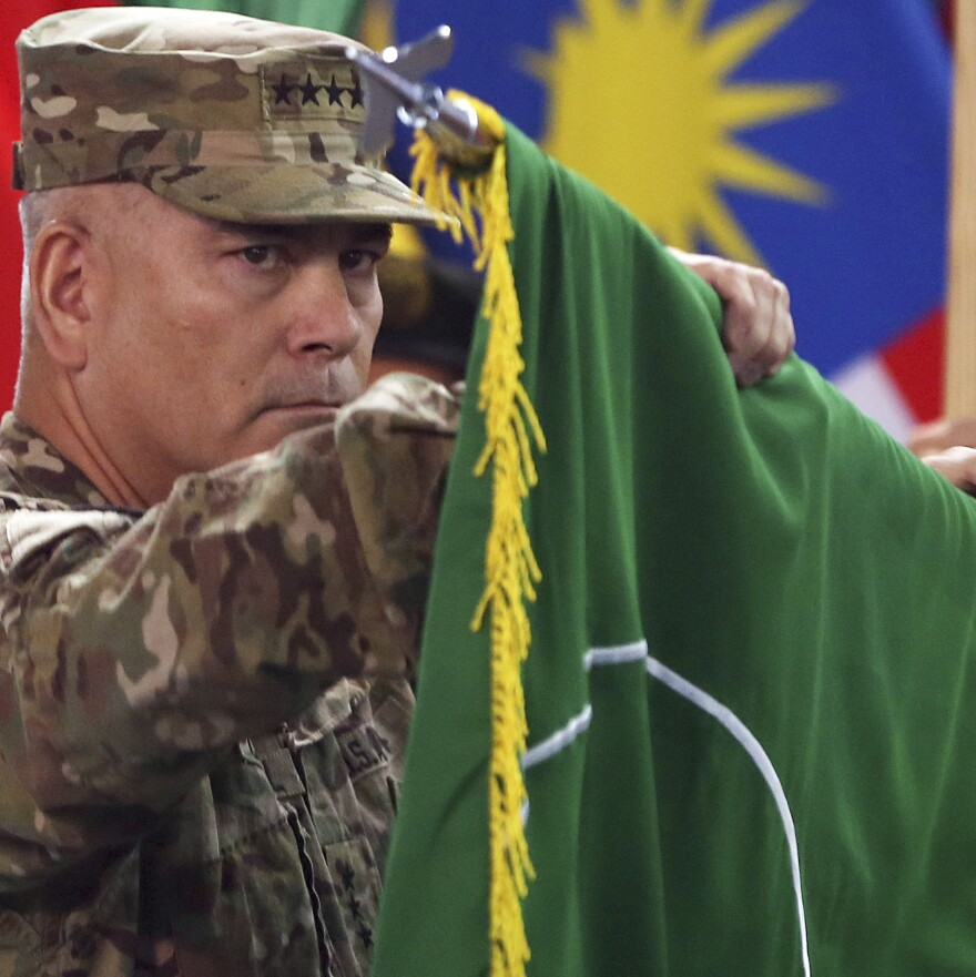 """Commander of the International Security Assistance Force (ISAF), Gen. John Campbell opens the """"Resolute Support"""" flag during a ceremony at the ISAF headquarters in Kabul on  Sunday."""