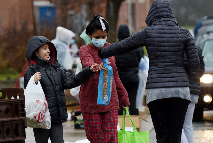 Volunteers from the Baltimore Hunger Project pass out food to people in need outside of Padonia International Elementary school on December 4, 2020 in Cockeysville, Maryland. (OLIVIER DOULIERY/AFP via Getty Images)