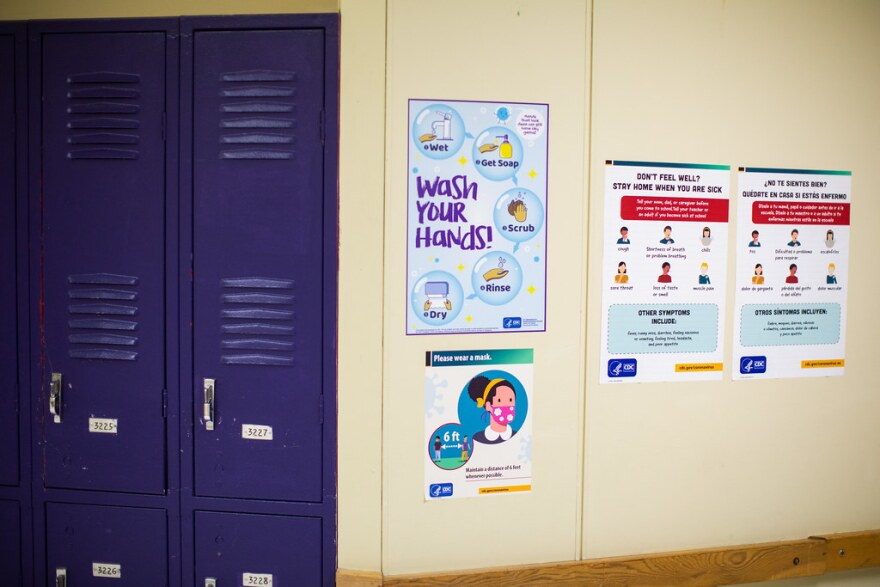 Signs in the hallway of the Liberal Arts and Science Academy tell people to wear masks and wash their hands.