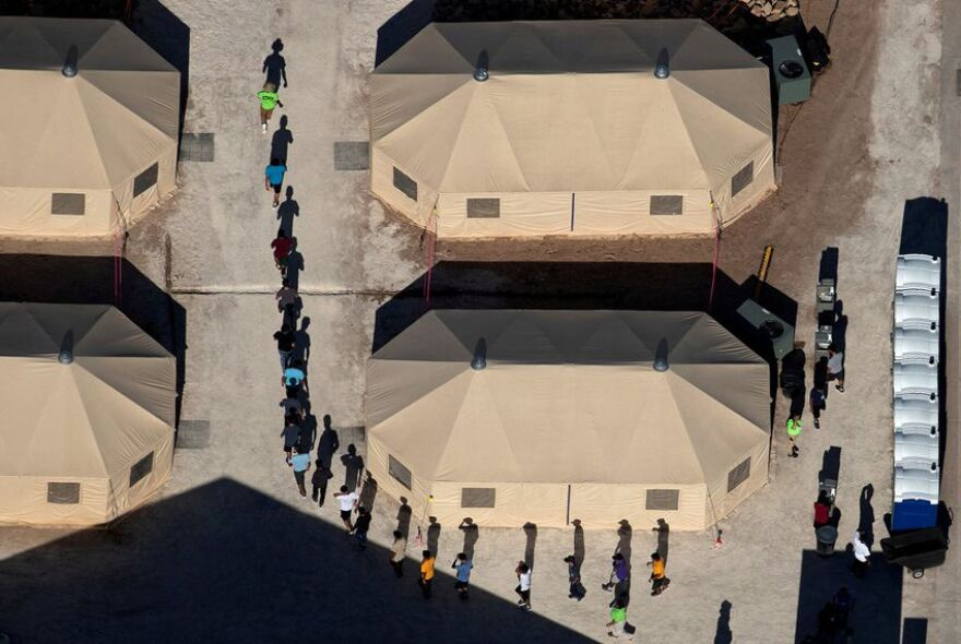 Staff lead immigrant children between tents at a detention facility next to the Mexican border in Tornillo in June.