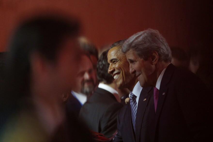 President Obama (center) and Secretary of State John Kerry (right) attend Monday's opening ceremony of the United Nations Climate Change Conference in the Paris suburb of Le Bourget.