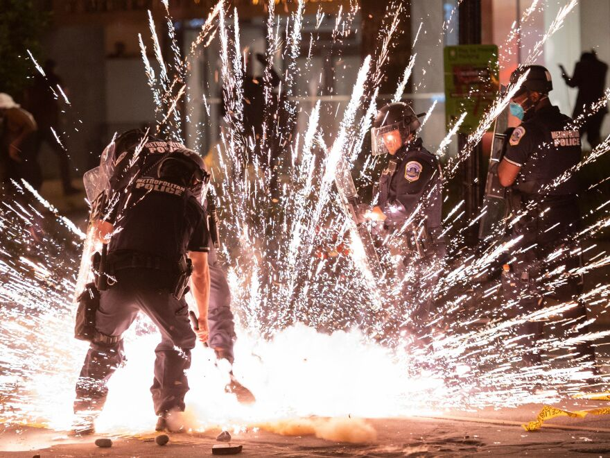 A firecracker thrown by protesters explodes among police officers near the White House.