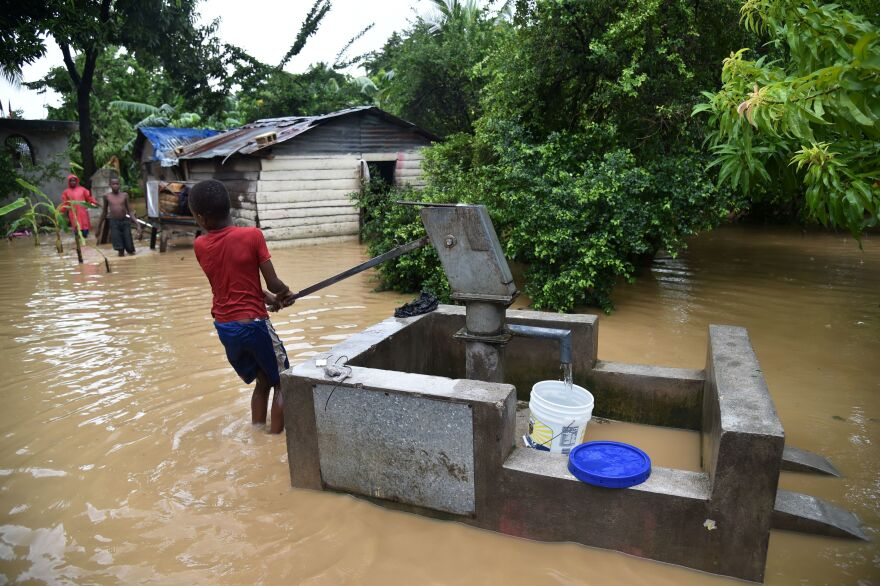 A boy pumps water close to his family's flooded home in Leogane on Wednesday.