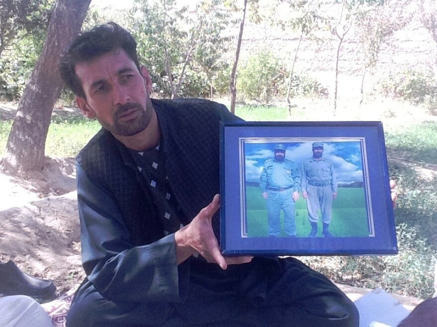 Mohammed Naeem, a driver, holds up a framed photo of two relatives he says were killed by militant leader Abdullah near the western city of Herat.