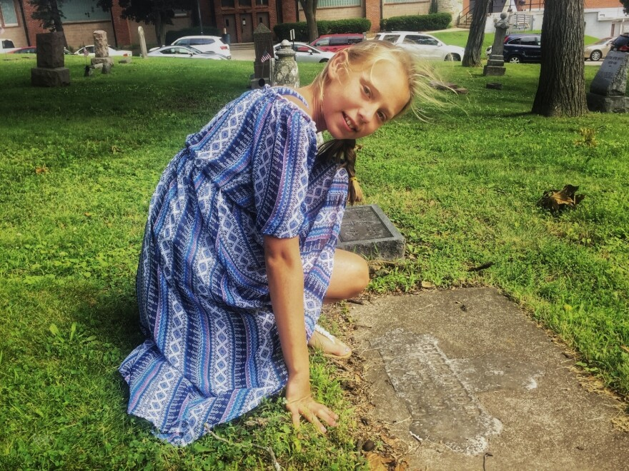 Laila Ericksen, 10, kneels at one of the historic grave markers on the grounds of St. John Chrysostom church, in Delafield, Wis. The town's founder, Charles Delafield, is buried here.