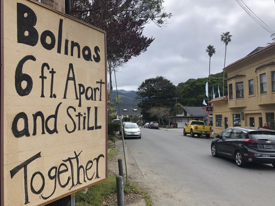 A sign about being 6 feet apart is posted along the main road through Bolinas, Calif. Residents are undergoing testing as part of a coronavirus study.