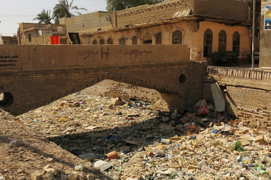 A canal along Basra's Shanashiel Street is covered in floating trash. The city was known as the Venice of the Middle East because of its beauty and canals. Decades of neglect have left it in ruins.
