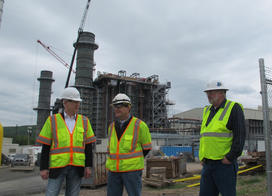 Bill Pentak of Panda Power Funds (left), Plant Manager John Martin (center) and Construction Manager Rob Risher (right) stand in front of the construction site for the new Panda Liberty gas power plant in Towanda, Penn. The plant, expected to come online in early 2016, was deliberately sited on top of the Marcellus Shale to take advantage of the cheap, abundant gas.