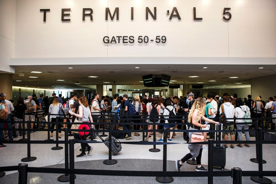 Passengers walk through a TSA checkpoint area at Los Angeles International Airport. Security experts say making airports safer is a huge challenge because public areas are designed for commerce.