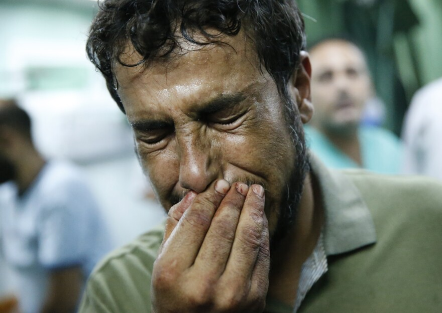 A Palestinian man cries after bringing a child, wounded in a strike on a compound housing a U.N. school, to the emergency room of the Kamal Adwan hospital in the Gaza Strip on Thursday.
