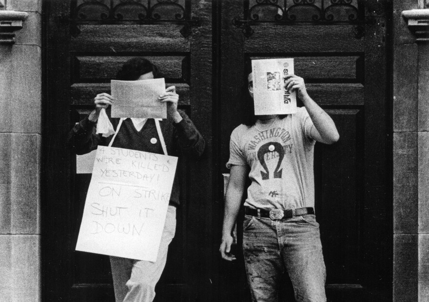 "Two Wash U students protest the Vietnam War following the Kent State shootings. The placard at left reads in part, ""Four students were killed yesterday."""