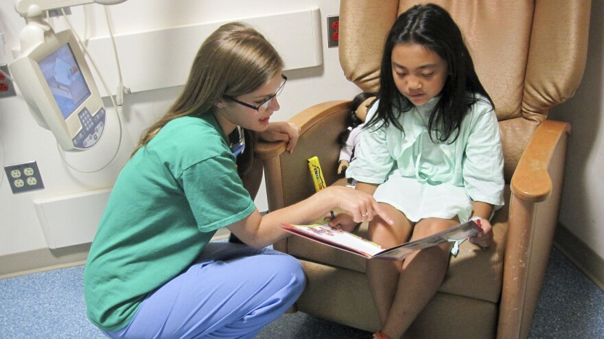 Child life specialist Kelly Schraf helps to put at ease Yoselyn Gaitan, 8, who had surgery on her cleft palate, at Children's National Medical Center in Washington, D.C.