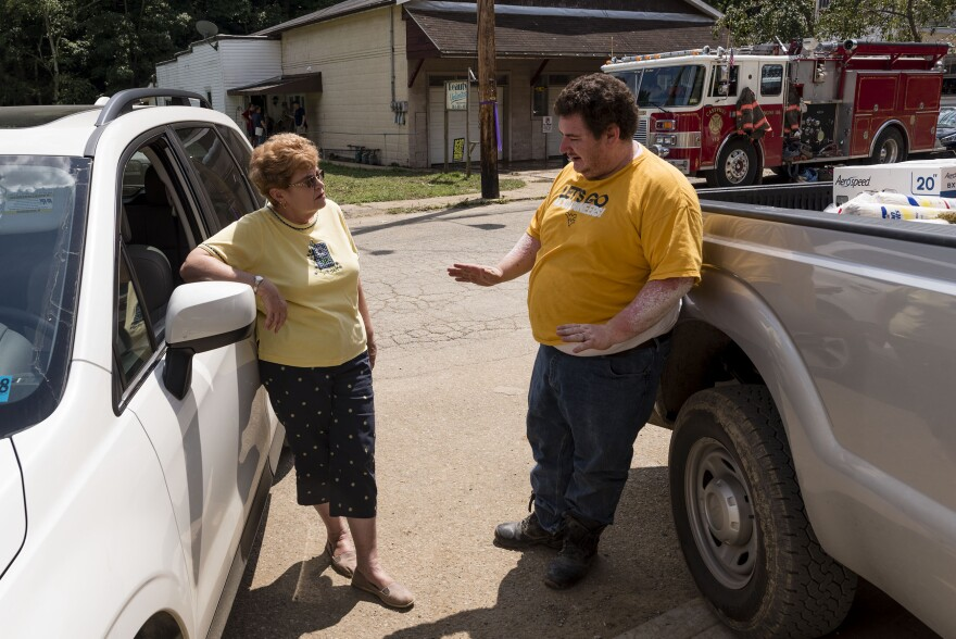 Hundred VFD President Johanna Lemasters and volunteer Jason Miller talk outside the VFD's new, but recently flooded, building in Hundred, W.Va.