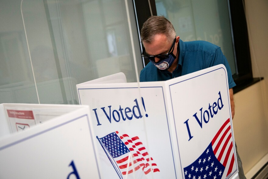 A man wears a face mask featuring the seal of Virginia as he fills out his ballot at an early voting site in Arlington, Virginia, U.S., September 18, 2020.