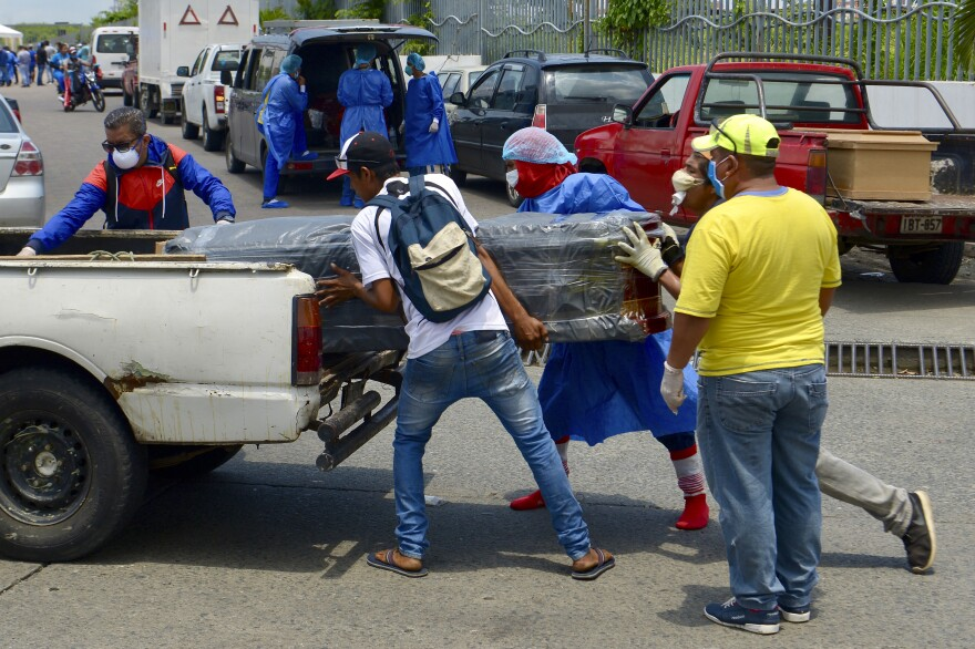 Men load a coffin onto a pickup truck in front of General del Guasmo Sur Hospital in Guayaquil, Ecuador. The port city is the most affected by COVID-19 in the country. Corpses lie in apartments for days and morgues are overcrowded. The city administration requested four refrigerated containers in which the corpses can be temporarily stored.