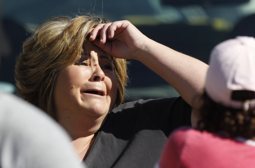 <p>An onlooker reacts near the site where six people were killed and three were wounded in a shooting at a hair salon in Seal Beach, Calif.</p>
