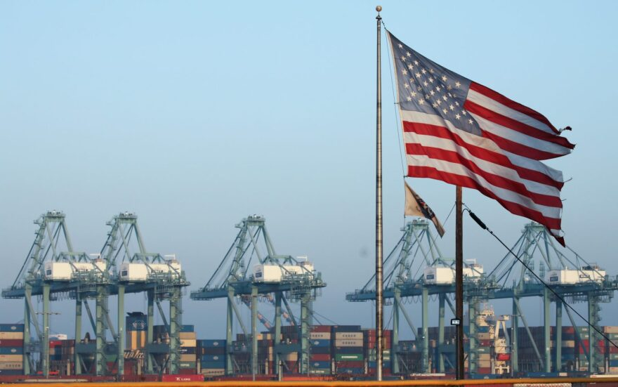 An American flag flies nearby with shipping containers stacked at the Port of Los Angeles in the background, which is the nation's busiest container port.