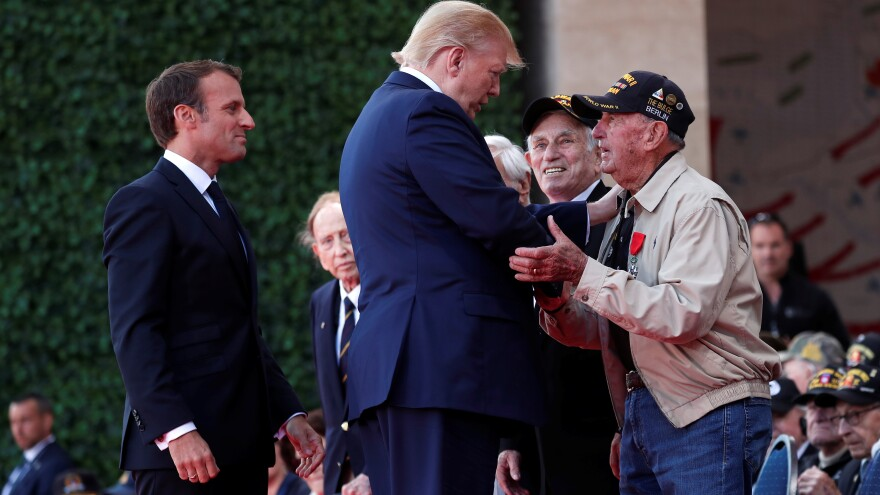 President Trump and French President Emmanuel Macron greet a U.S. veteran during the D-Day commemoration at the Normandy American Cemetery and Memorial in Colleville-sur-Mer, France.