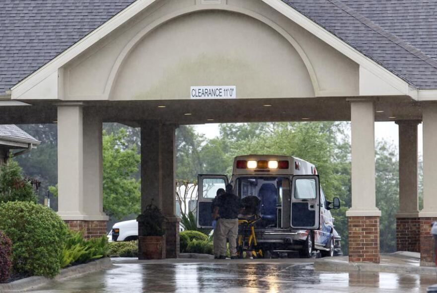 Paramedics disinfect a gurney in their ambulance before leaving a  nursing home.