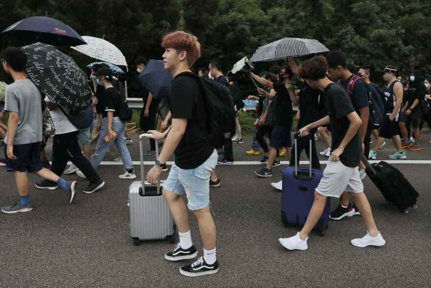 Protesters walk on a highway near Hong Kong's international airport following a protest against police brutality and the controversial extradition bill.