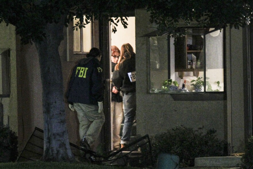 FBI agents search Thursday outside a home in Redlands, Calif., in connection with the San Bernardino shootings.