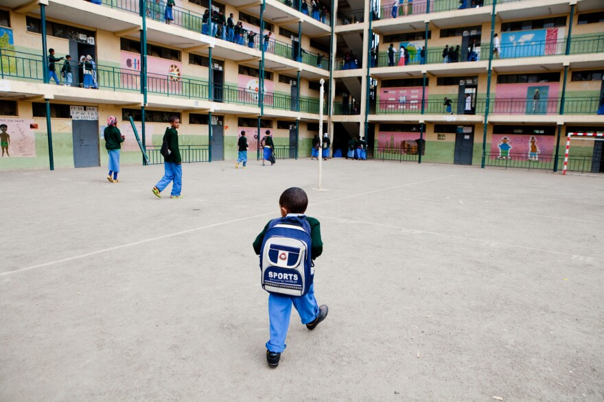 Sisay Gudeta walks to class after other kids have cleared the courtyard in Addis Ababa, Ethiopia, May 2013. He is afraid of being knocked over by kids playing and falling on his back.