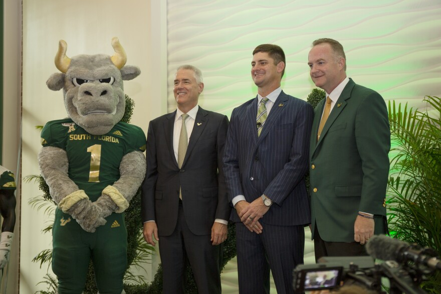 Bull mascot poses for picture with three men in suits.