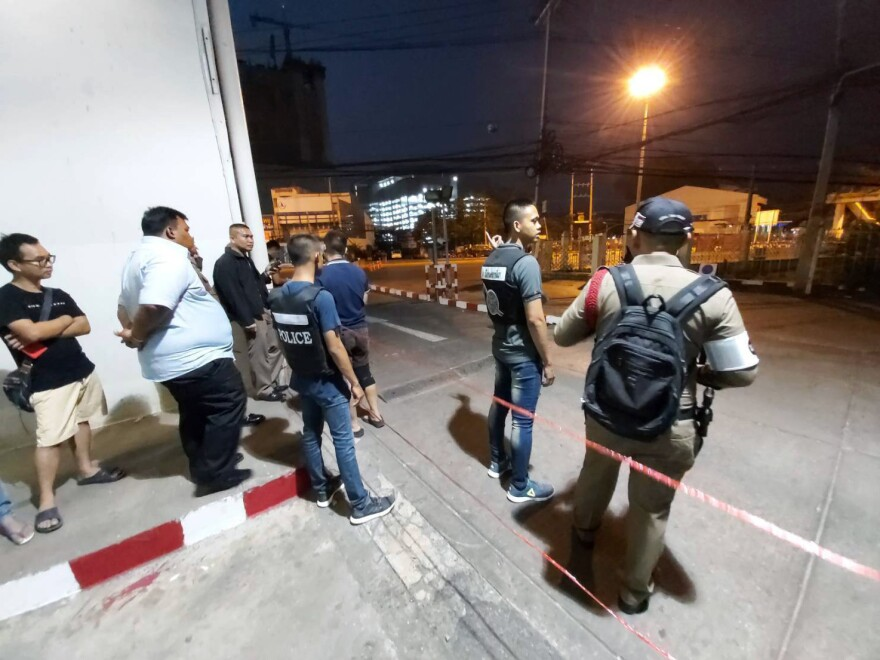 Police and bystanders stand near the scene of a shooting at the Terminal 21 mall, in Nakhon Ratchasima, Thailand on Saturday.