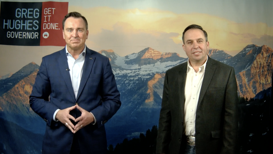 Two men in suits stand in front of a photo backdrop of mountains.