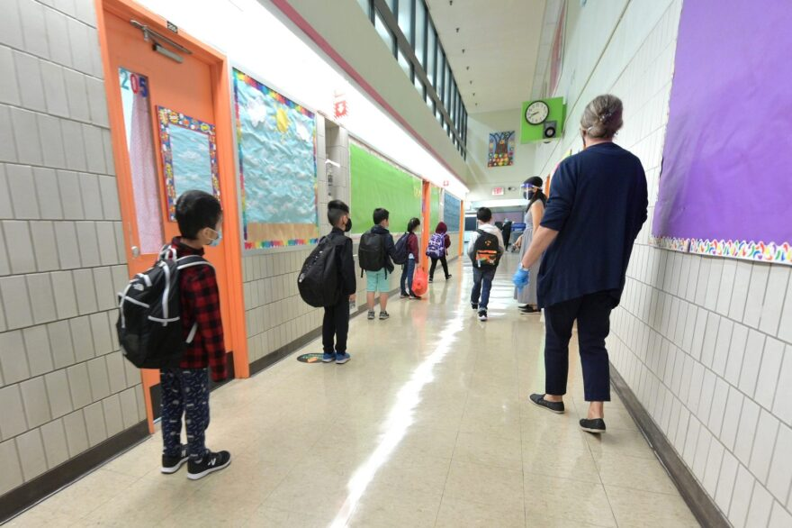 Students line up before walking into class on a day of in=person learning at Yung Wing School P.S. 124 in New York City. The start of in-person learning was delayed in New York City schools via a phased in reopening.