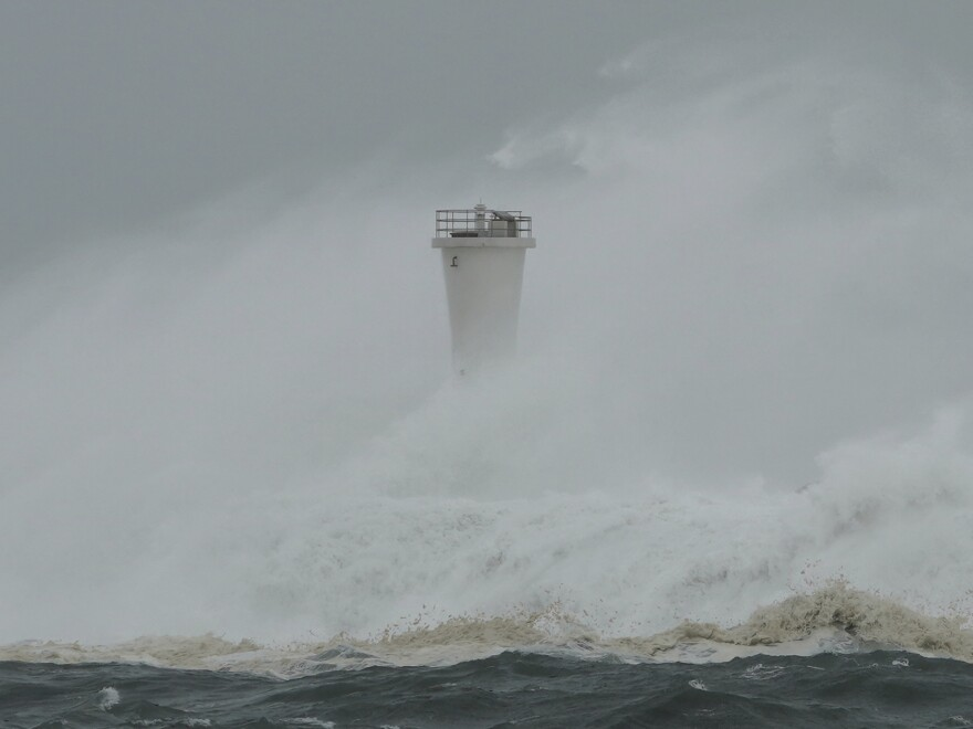 Surging waves hit against the breakwater and a lighthouse as Typhoon Hagibis approaches at a port in town of Kiho, Mie prefecture, central Japan on Saturday. (AP Photo/Toru Hanai)