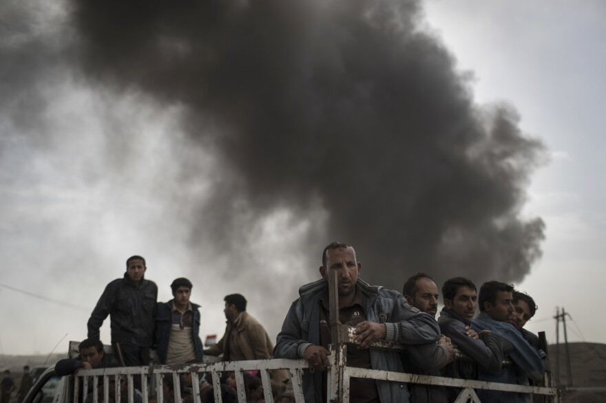 Displaced people stand on the back of a truck Tuesday at a checkpoint near Qayara, south of Mosul, Iraq,