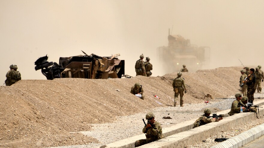 U.S. soldiers keep watch near the wreckage of their vehicle at the site of a Taliban suicide attack in Kandahar in August 2017.