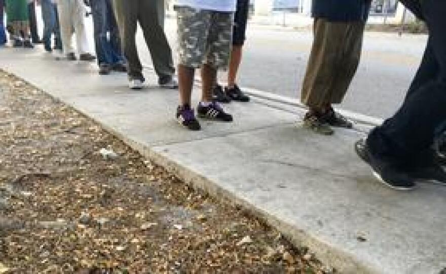 Homeless people line up for food in downtown Miami.