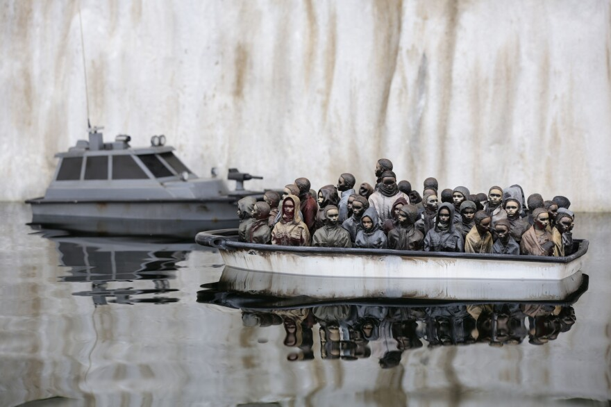 "This art exhibit shows a boat packed with migrants floating in a pond at Banksy's ""bemusement park"" called Dismaland. Now, the park is being dismantled and the materials are being sent to a refugee camp in France to be used for building shelters."