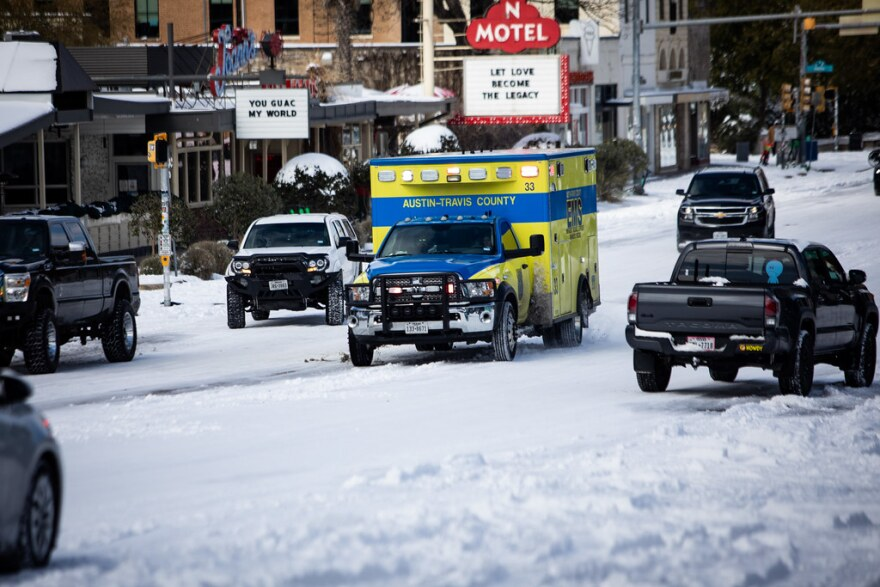 An Austin-Travis County EMS ambulance moves down South Congress Avenue during Monday's winter storm.