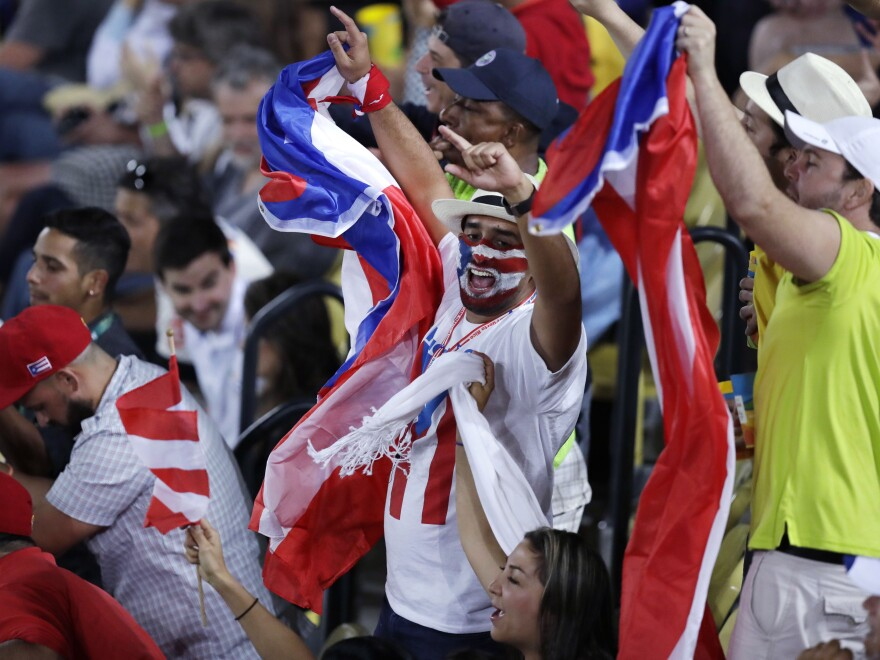 Fans cheer during the final round match between Monica Puig of Puerto Rico and Angelique Kerber of Germany at the 2016 Summer Olympics in Rio de Janeiro, Brazil.