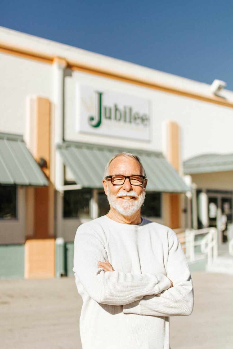 """A bespectacled man stands in front of a storefront that says """"Jubilee""""."""