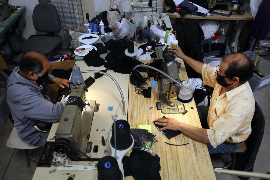 Two workers sew face masks at SPIbelt in Austin.