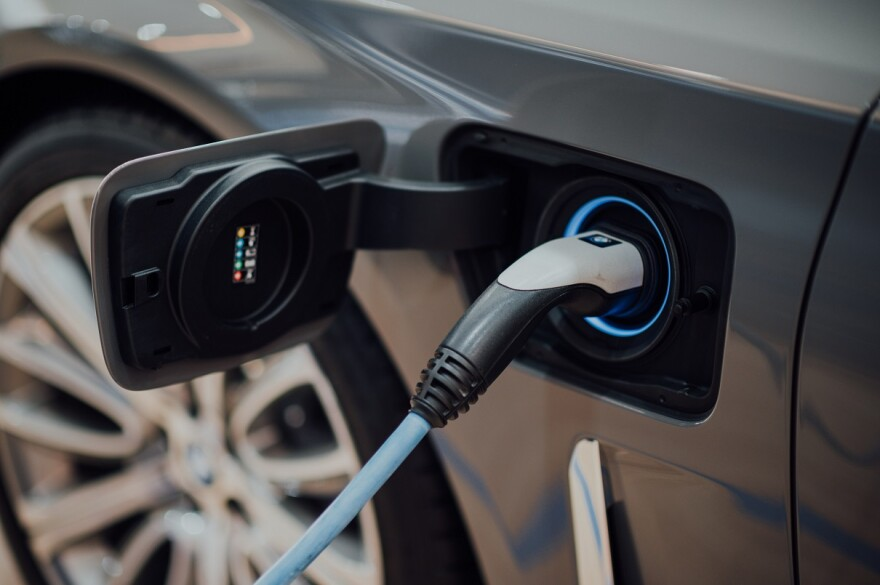 Electric vehicle is plugged into a charging outlet