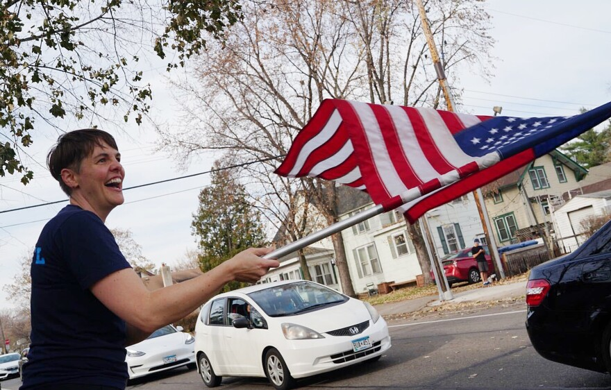 <strong>MINNEAPOLIS</strong>: Becky Kuehn waves a flag on the sidewalk to passing cars as she celebrates Joe Biden's victory in the presidential election in south Minneapolis.