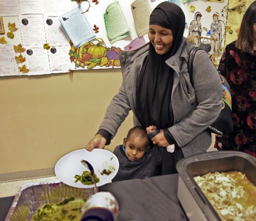 One of the International Institute's students and her young son go through the food serving line for the traditional Thanksgiving dinner that the Institute served Tuesday. For some of the 400 English and citizenship students, this was their first Thanksgi