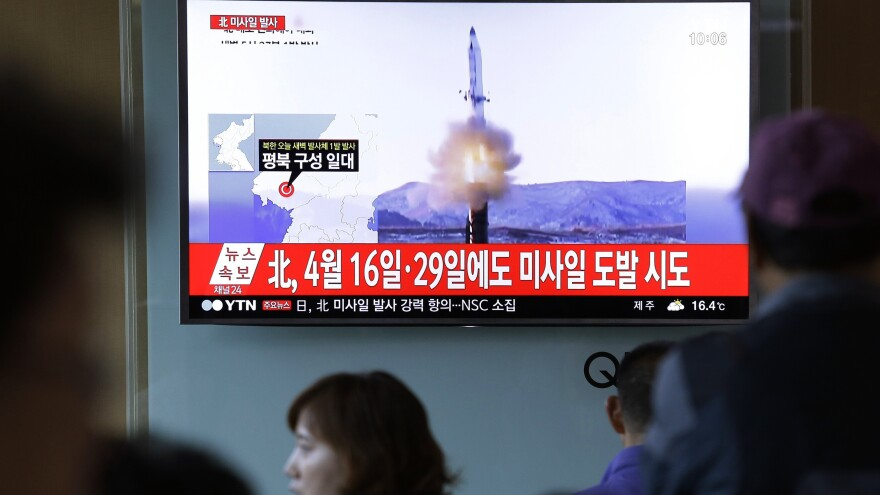 People watch a TV news program showing a file image of a previous missile launch conducted by North Korea at the Seoul Railway Station in Seoul. North Korea on Sunday test-launched a ballistic missile that landed in the Sea of Japan, the South Korean, Japanese and U.S. militaries said.