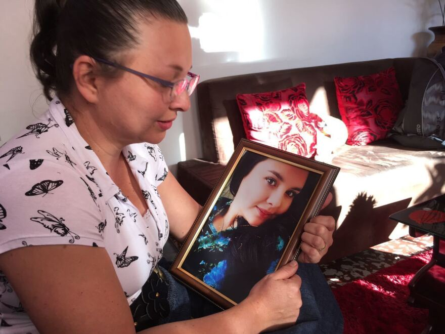 Doris Cuervo holds a photo of her daughter, Ximena Lopez. She died after visiting a spa for an injection to give her a curvier behind.
